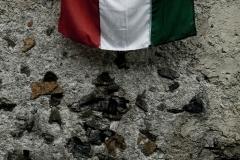 Malesco (VB), Frazione di Finero, Italia. La bandiera italiana appesa sul muro del cimitero in occasione della  commemorazione del 16 giugno 2010 dei 15 martiri di Finero, fucilati di fronte a questo muro il 23 giugno 1944.